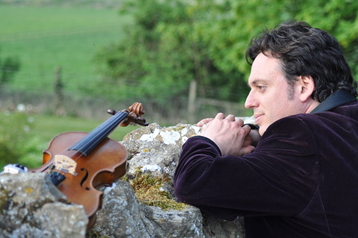 Image of Andrew Hubbard looking over a wall on which is laid his violin